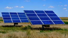 ground solar panels in a field under a blue sky